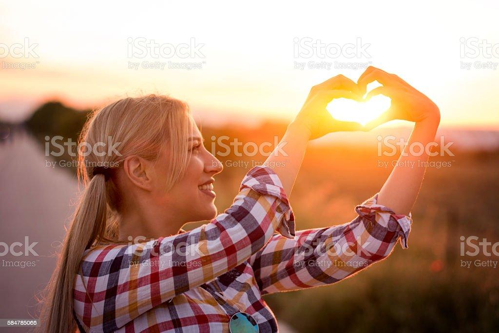 Stunning girl heart framing sun with hands stock photo