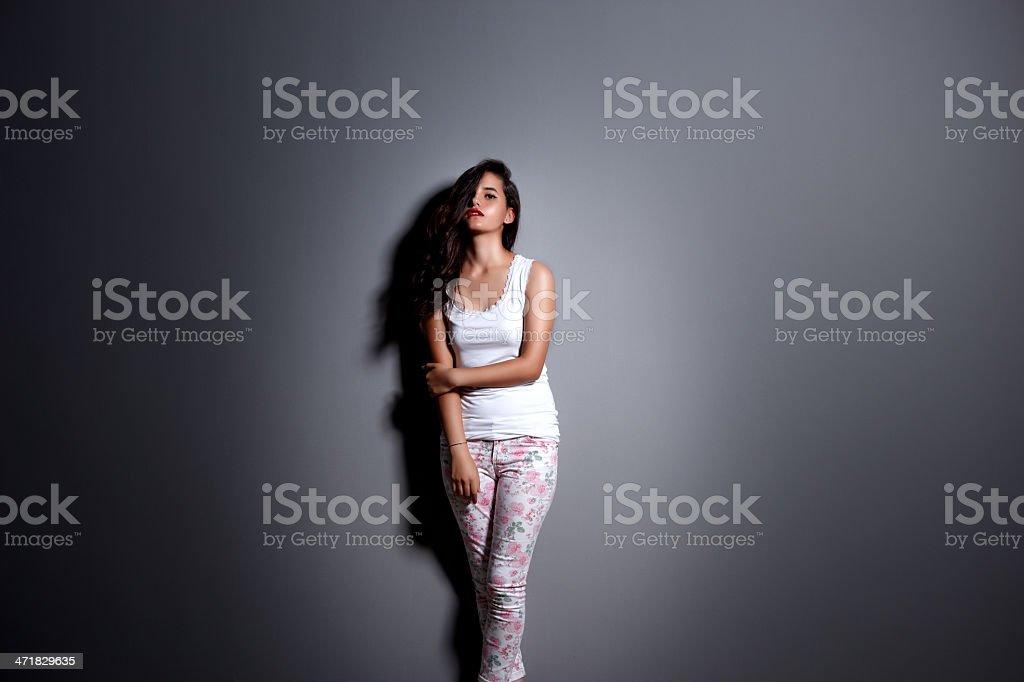 Stunning girl posing against gray royalty-free stock photo