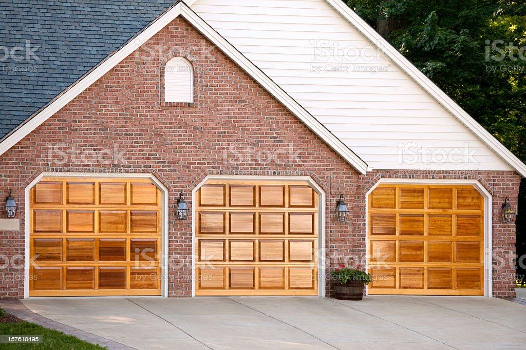 Stunning Hardwood Garage Doors, Attached Three Stall, Brick, Vinyl royalty-free stock photo