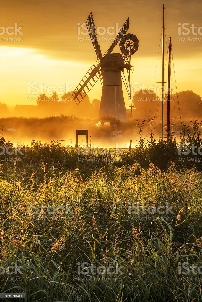 Stunning landscape of windmill and river at dawn stock photo