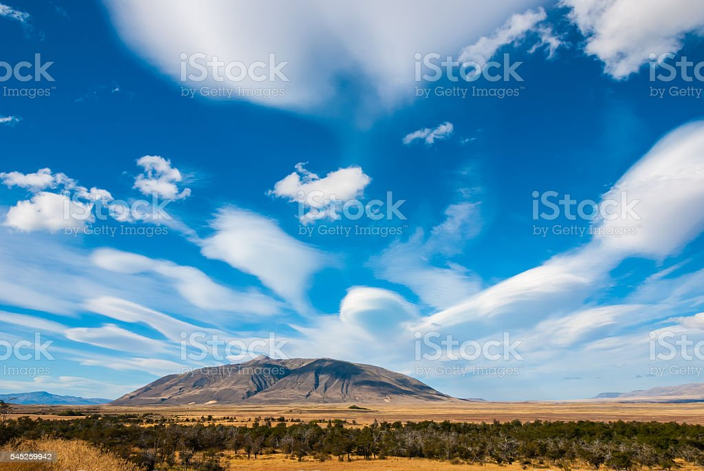 Stunning lenticular cloud formations over a massive glacial mound. stock photo