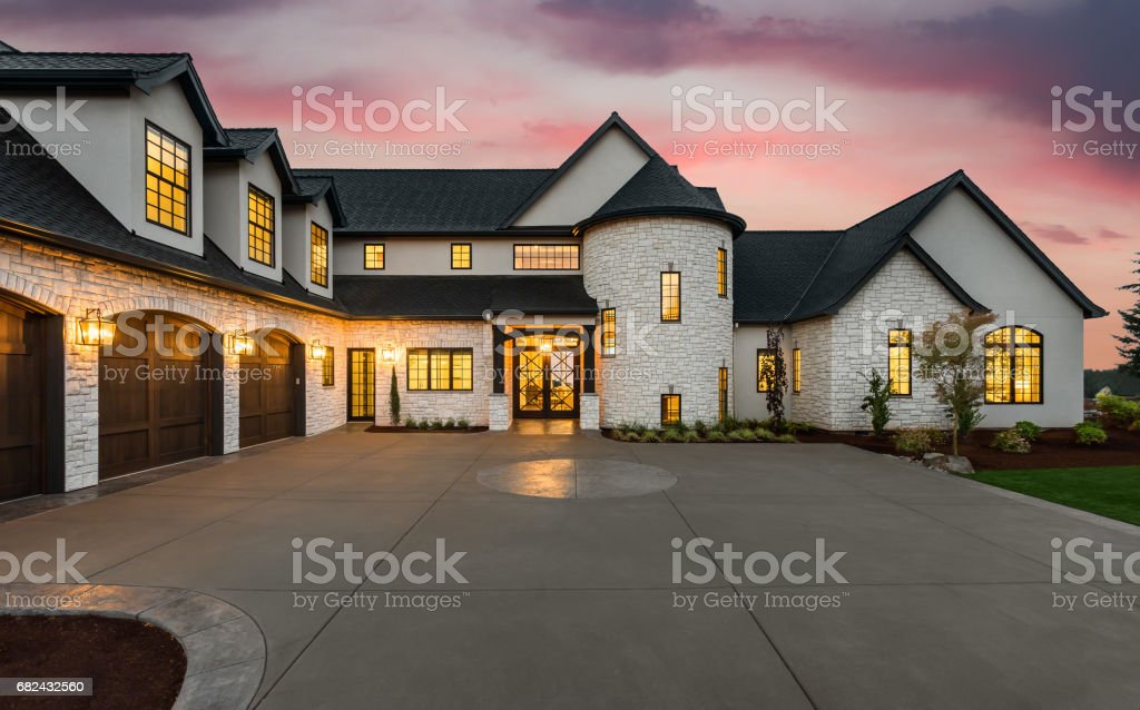 new luxury home with three car garage, large driveway and glowing...