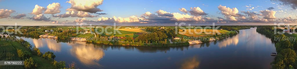 Stunning panoramic landscape with clouds reflected in tranquil river stock photo