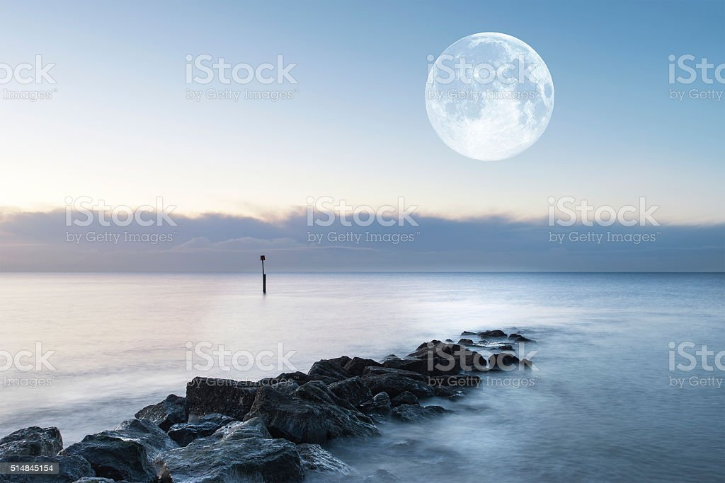 Stunning sunrise landscape over rocks in sea with super moon stock photo