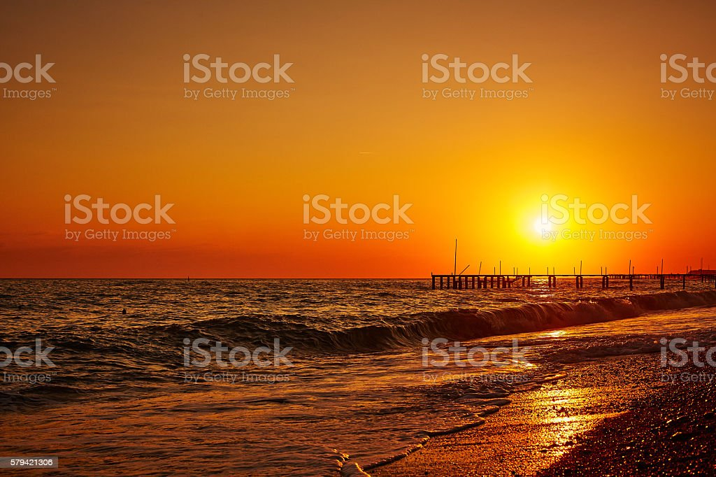 Stunning sunset with pier and sea waves stock photo