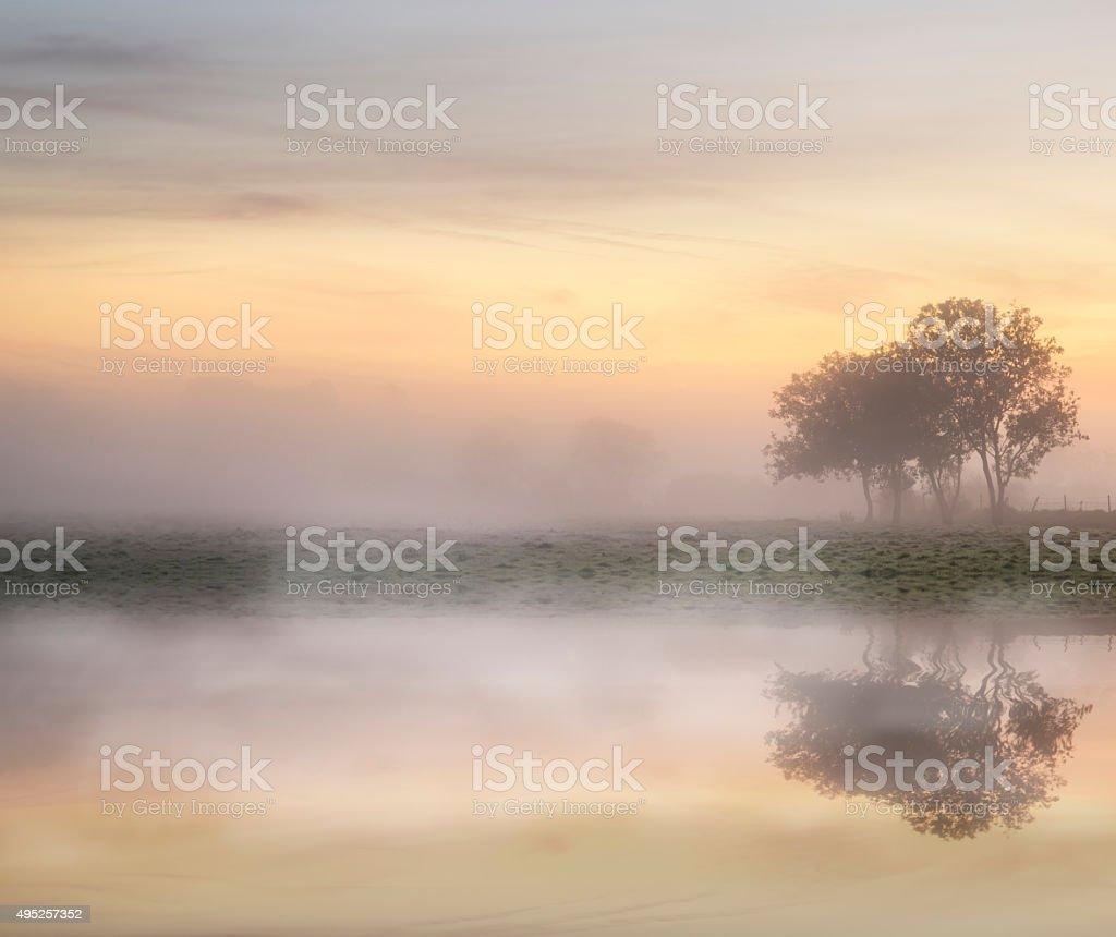 Stunning vibrant Autumn foggy sunrise English countryside landsc stock photo