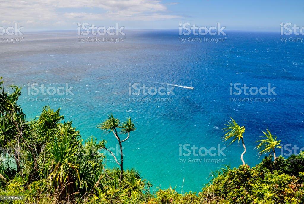 Stunning view from Kalalau Trail along Na Pali Coast on the Hawaiian island of Kauai. The 11 mile long trail along Na Pali Coast is the only way to reach Kalalau Beach. Clear ocean and a boat. stock photo