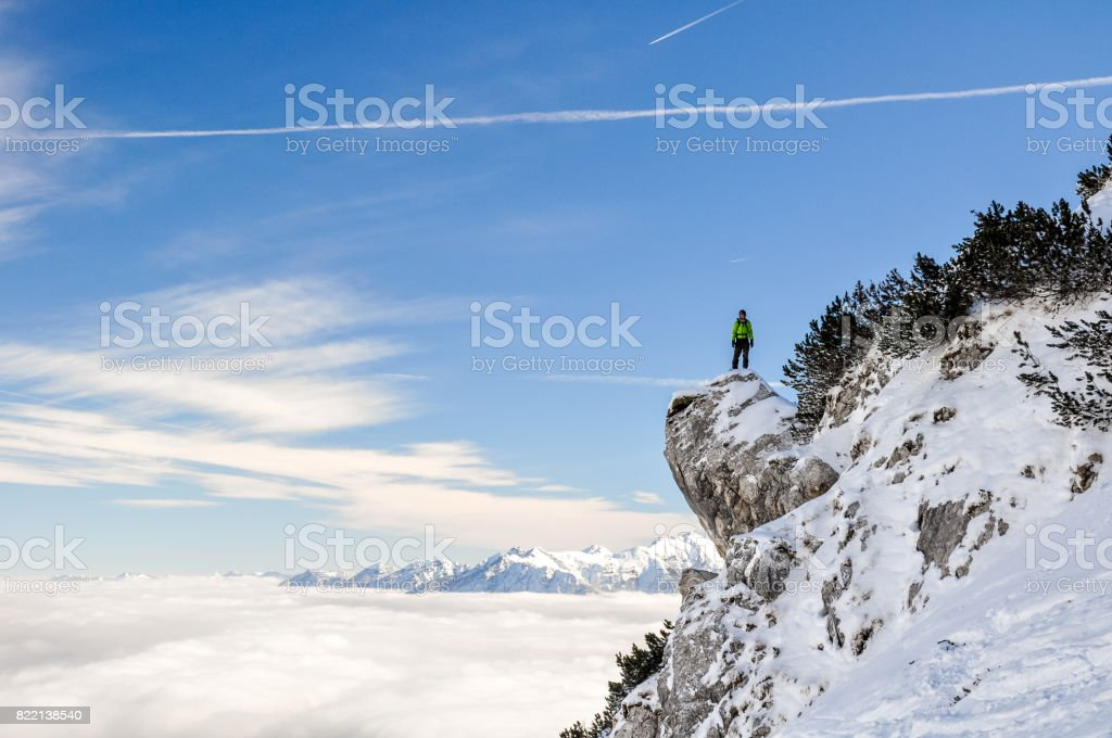 Stunning view of a hiker standing on a steep cliff near the Bavarian town of Garmisch Partenkirchen near Zugspitze mountain in Germany. Beautiful snow landscape in winter. Deep snow off piste slope. stock photo