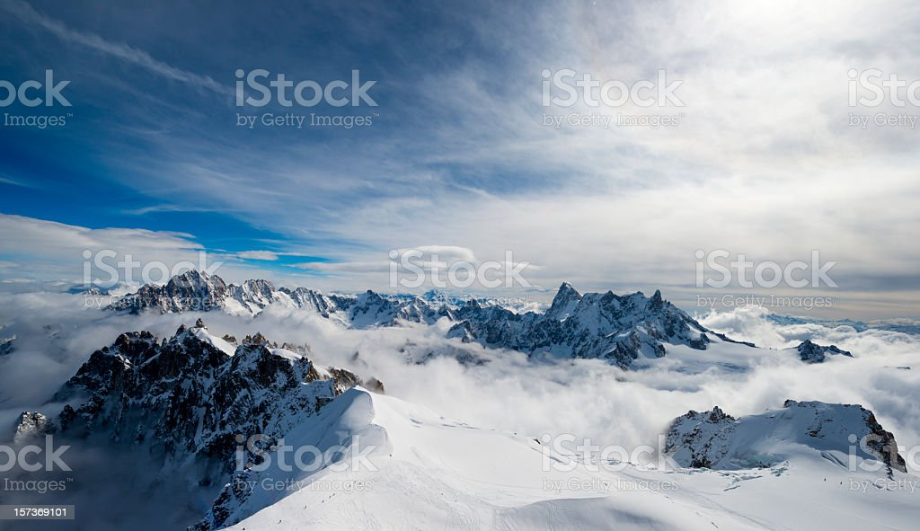 Stunning view of snowy mountain above clouds stock photo
