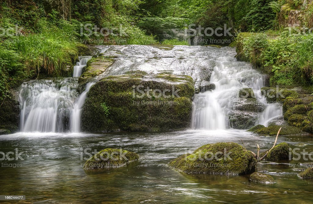 Stunning waterfall flowing over rocks through lush green forest royalty-free stock photo