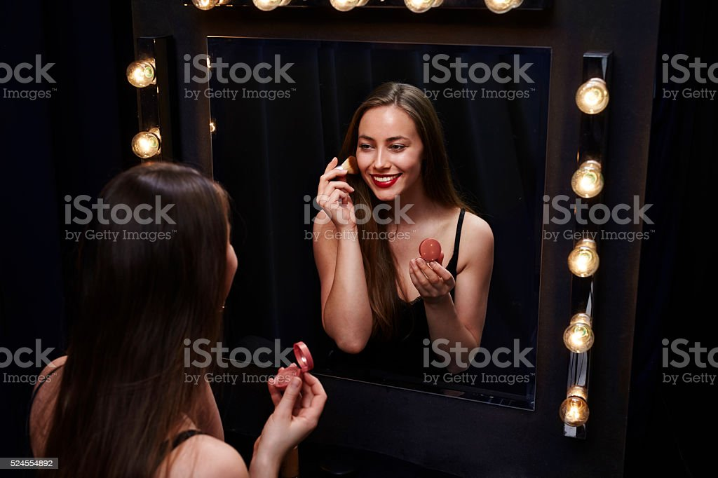 Stunning young woman with blusher in mirror stock photo