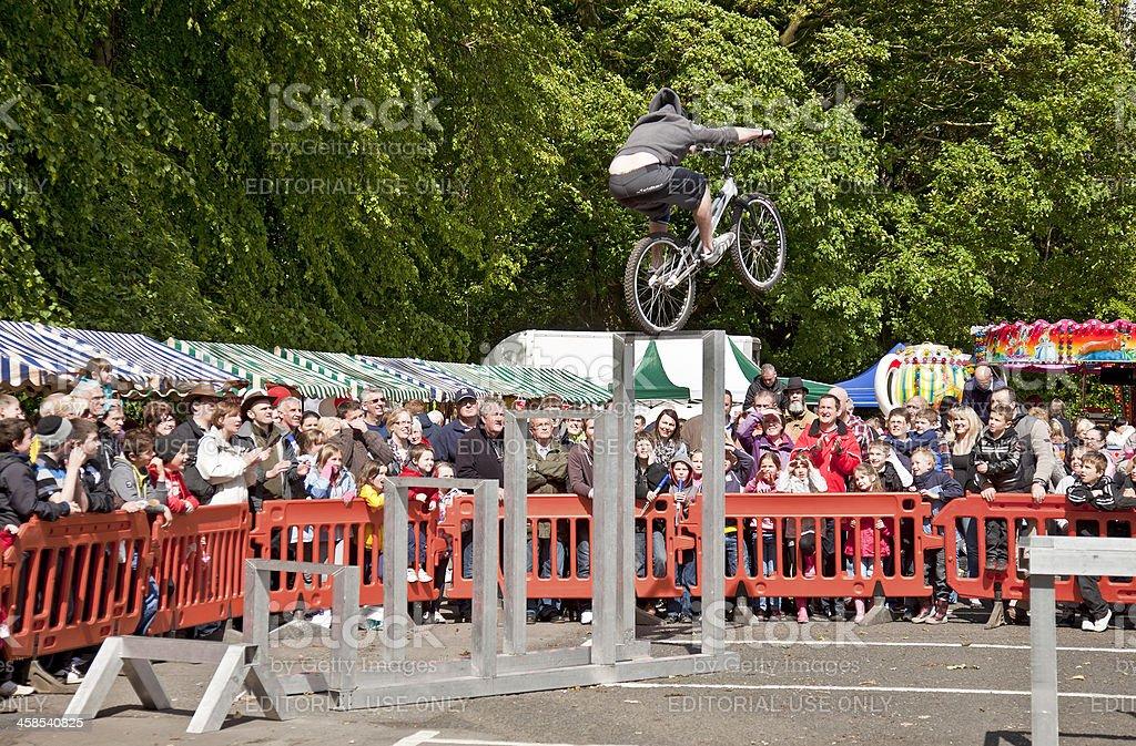 BMX stunt driver reaching the top of aluminium 'ladder' royalty-free stock photo