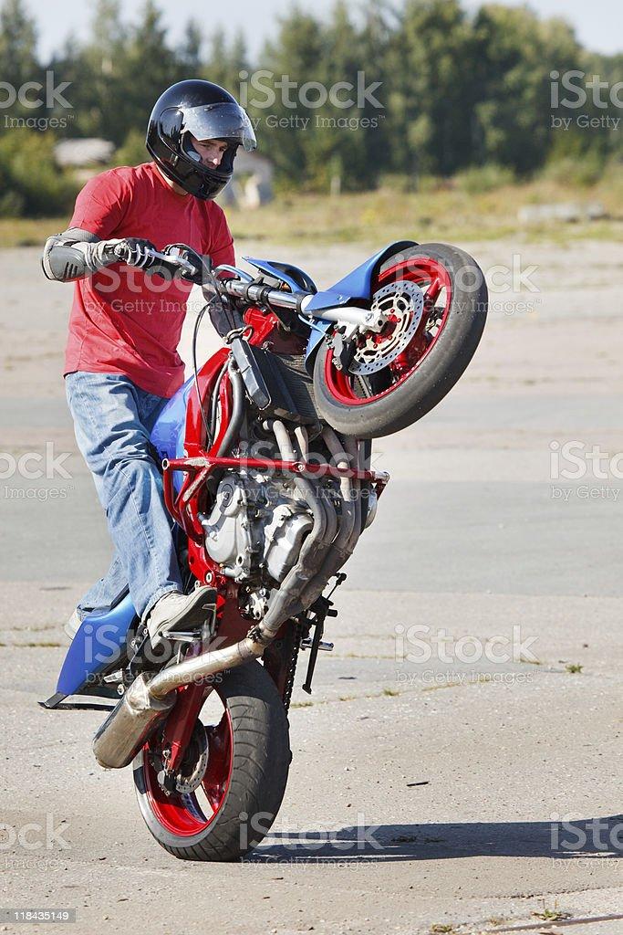 Stunt rider making wheelie royalty-free stock photo