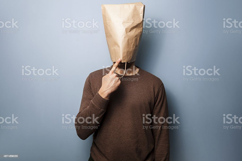 Stupid young man with bag over his head stock photo
