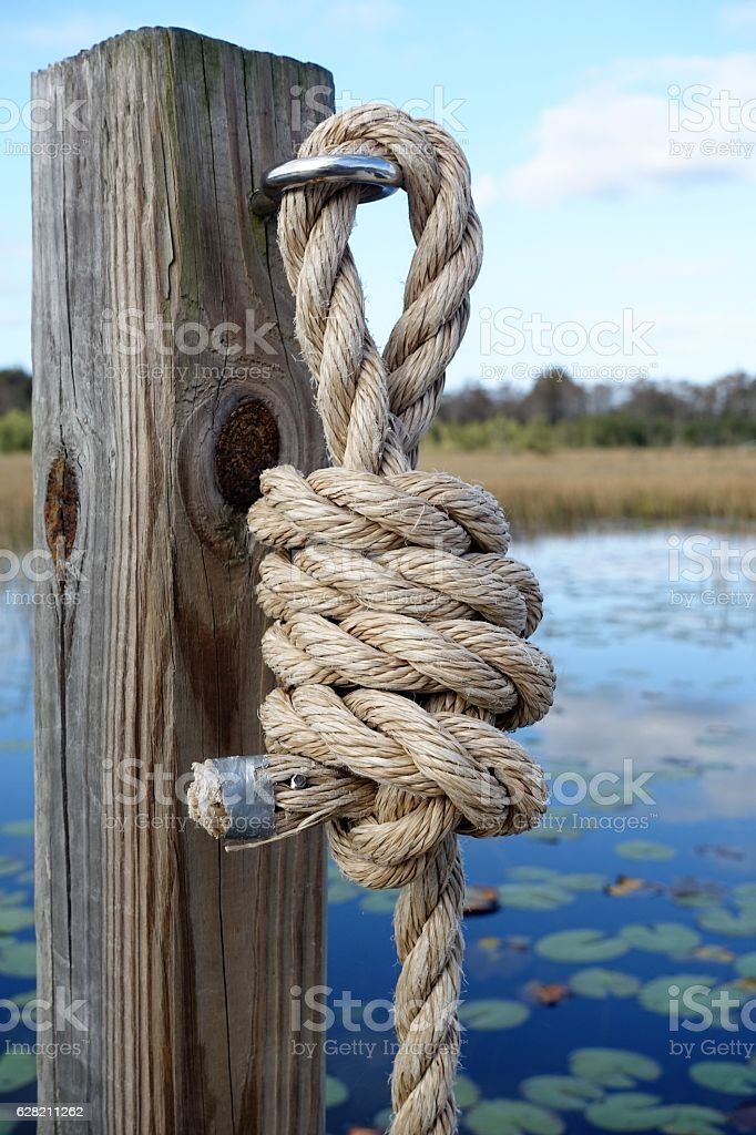 Sturdy rope knot on post stock photo