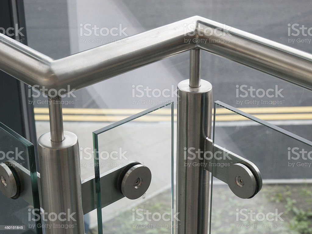 Sturdy silver metal handrail with glass in between stock photo