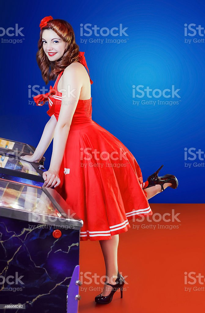 Style pinup girl in red dress, play pinball. stock photo