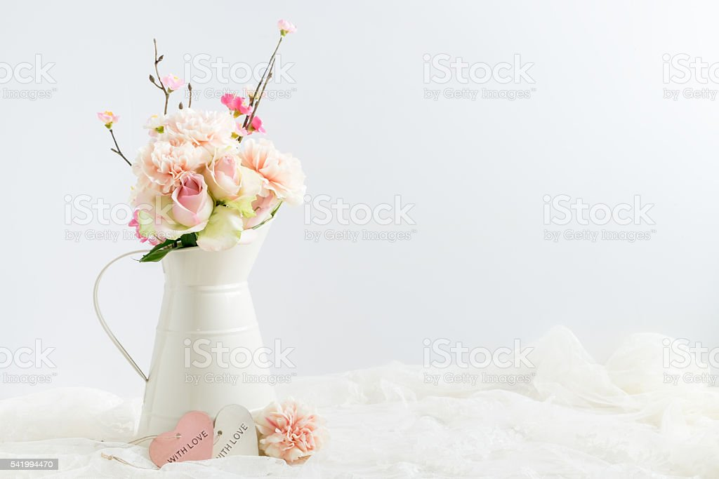 styled stock image of flowers in a cream jug stock photo