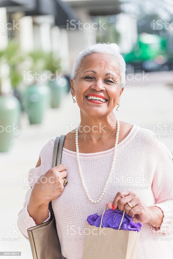 Stylish African American woman on sidewalk, out shopping stock photo