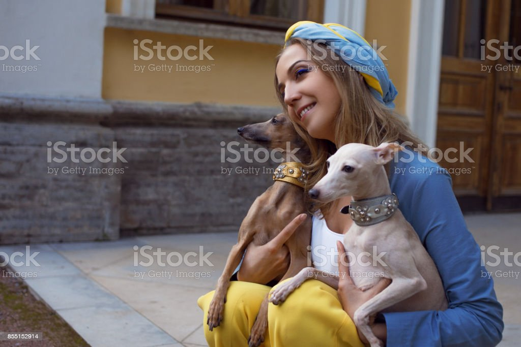 Stylish and beautiful young woman walks with the dogs
