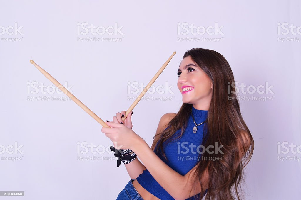 Stylish and trendy young woman holding drum sticks stock photo