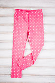 Stylish baby pink pants on the wooden background