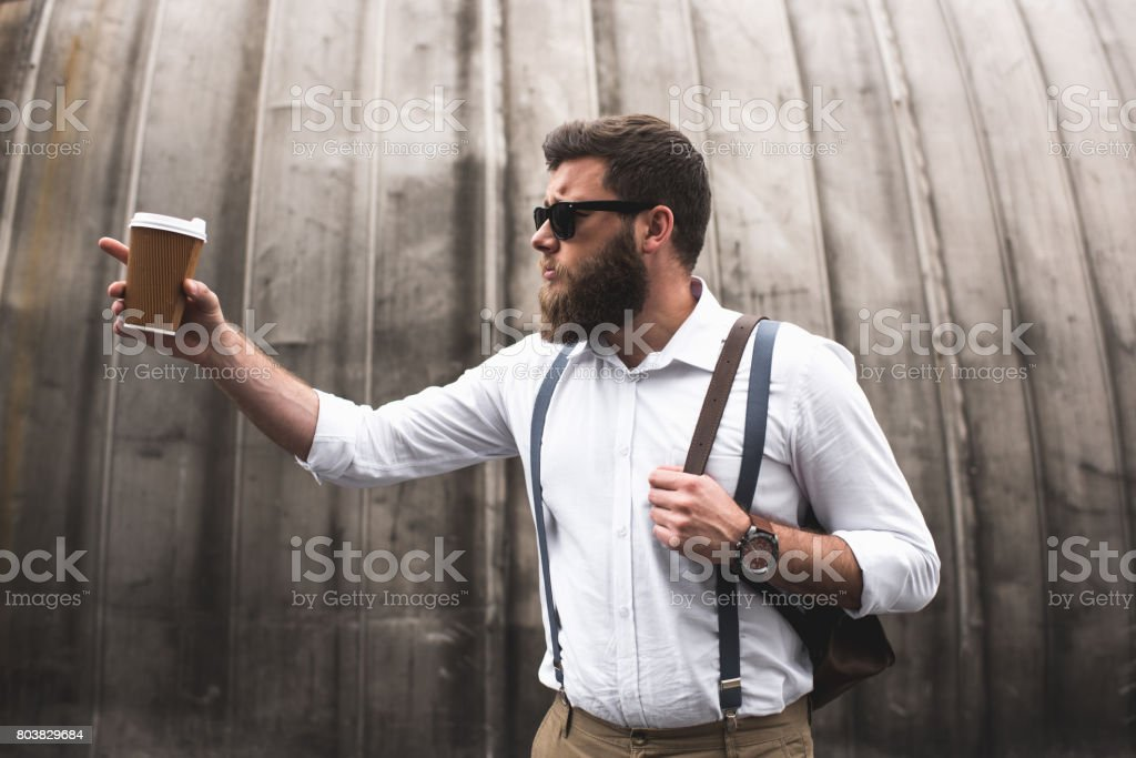 stylish bearded man with sunglasses and leather backpack holding disposable coffee cup and pointing somewhere stock photo