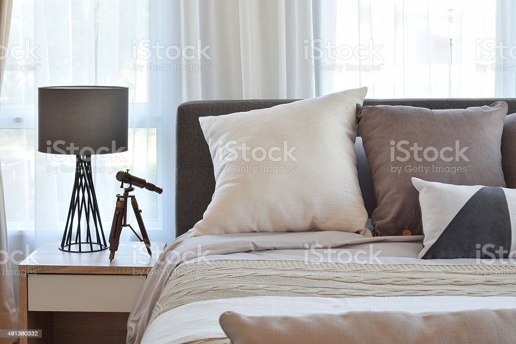 stylish bedroom interior design with brown patterned pillows on stock photo