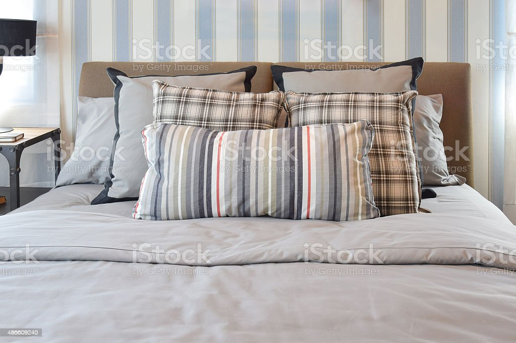 stylish bedroom interior design with striped pillows on bed and stock photo