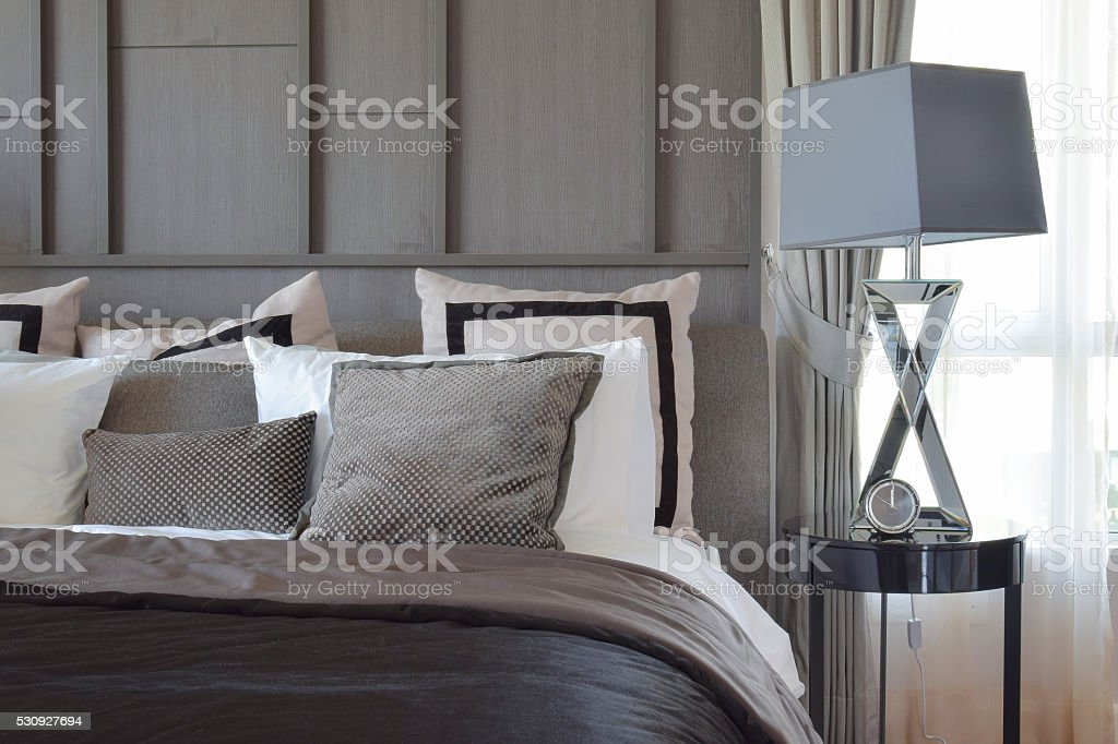 stylish bedroom with black patterned pillows on bed stock photo