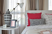 stylish bedroom with flower pattern pillows and decorative table lamp