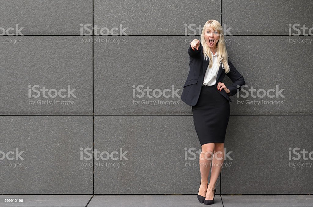 Stylish blond woman pointing at the camera stock photo