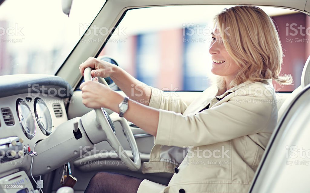 Stylish blonde woman smiling in a vintage car stock photo