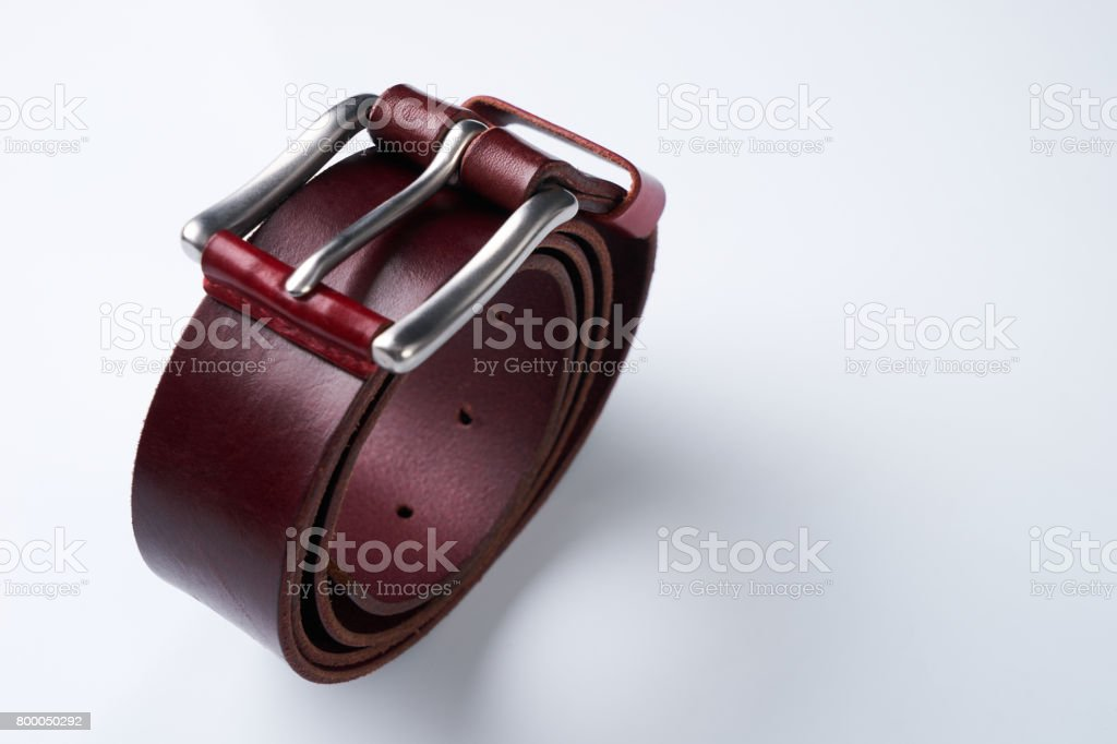 Stylish brown leather belt with a buckle isolated on white background. stock photo
