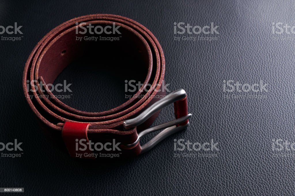 Stylish brown leather belt with a buckle on black textured leather background stock photo