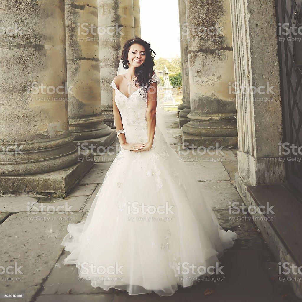 stylish brunette bride between columns stock photo