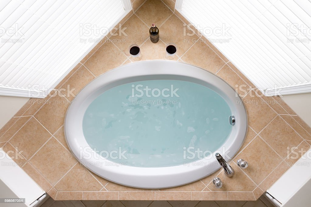 Stylish corner oval bathtub in a tile surround stock photo
