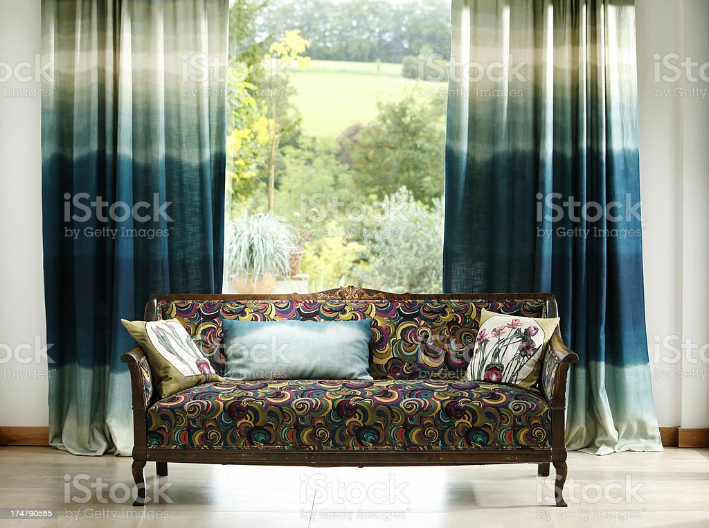 Stylish curtains with cushions on colourful chair in foreground royalty-free stock photo