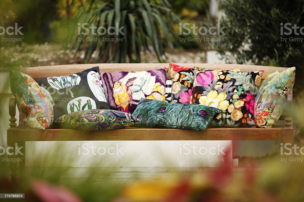 Stylish cushions on wooden seat placed in garden stock photo