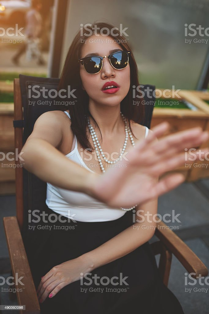Stylish female showing reluctance to be photographed stock photo