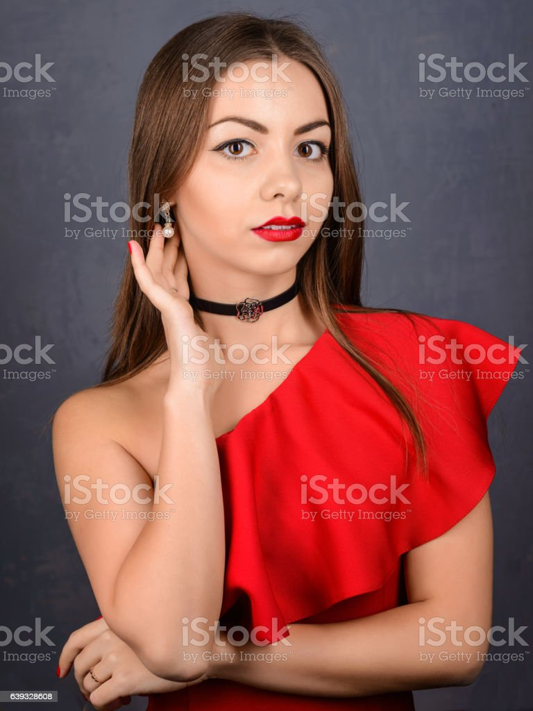 Stylish girl in red dress neck with black choker stock photo