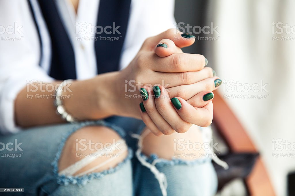 Stylish girl sitting in torn jeans and modern green nail stock photo