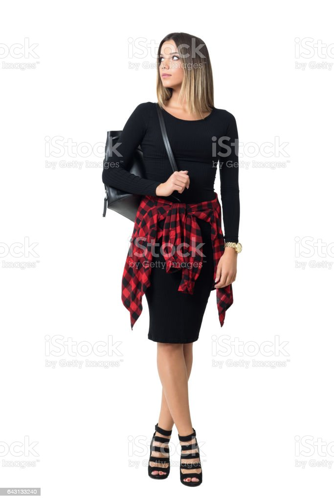 Stylish girl wearing heels carrying bag looking over the shoulder stock photo