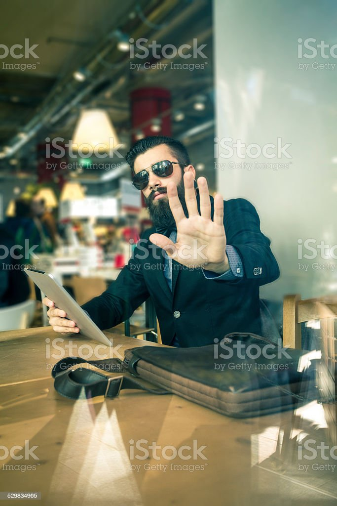 Stylish Hipster in a book-cafe protect his privacy stock photo