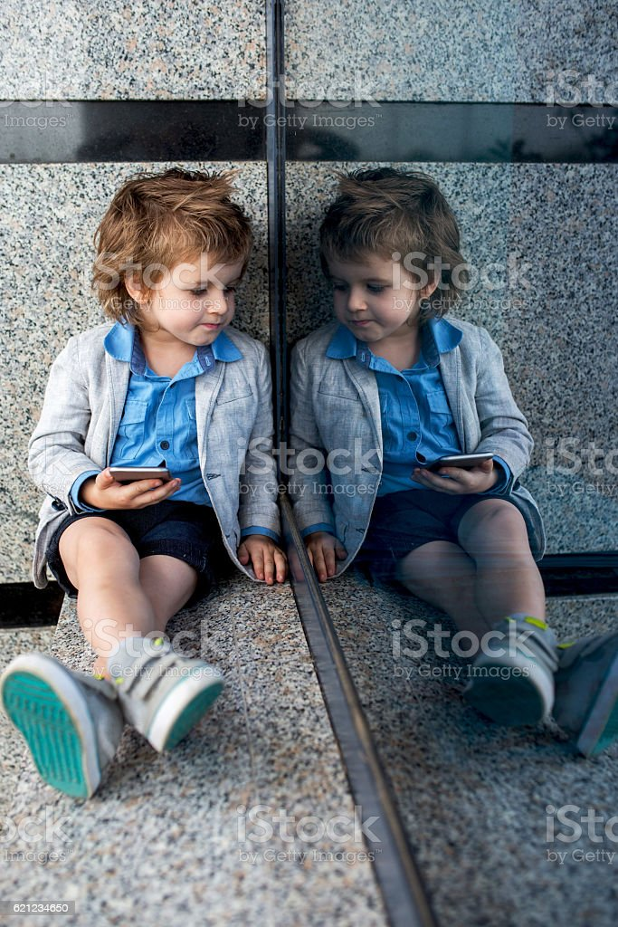 Stylish kid with cell phone thinking about something. stock photo