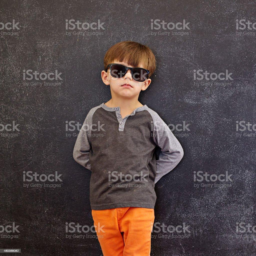 Stylish little boy wearing sunglasses leaning on a blackboard stock photo