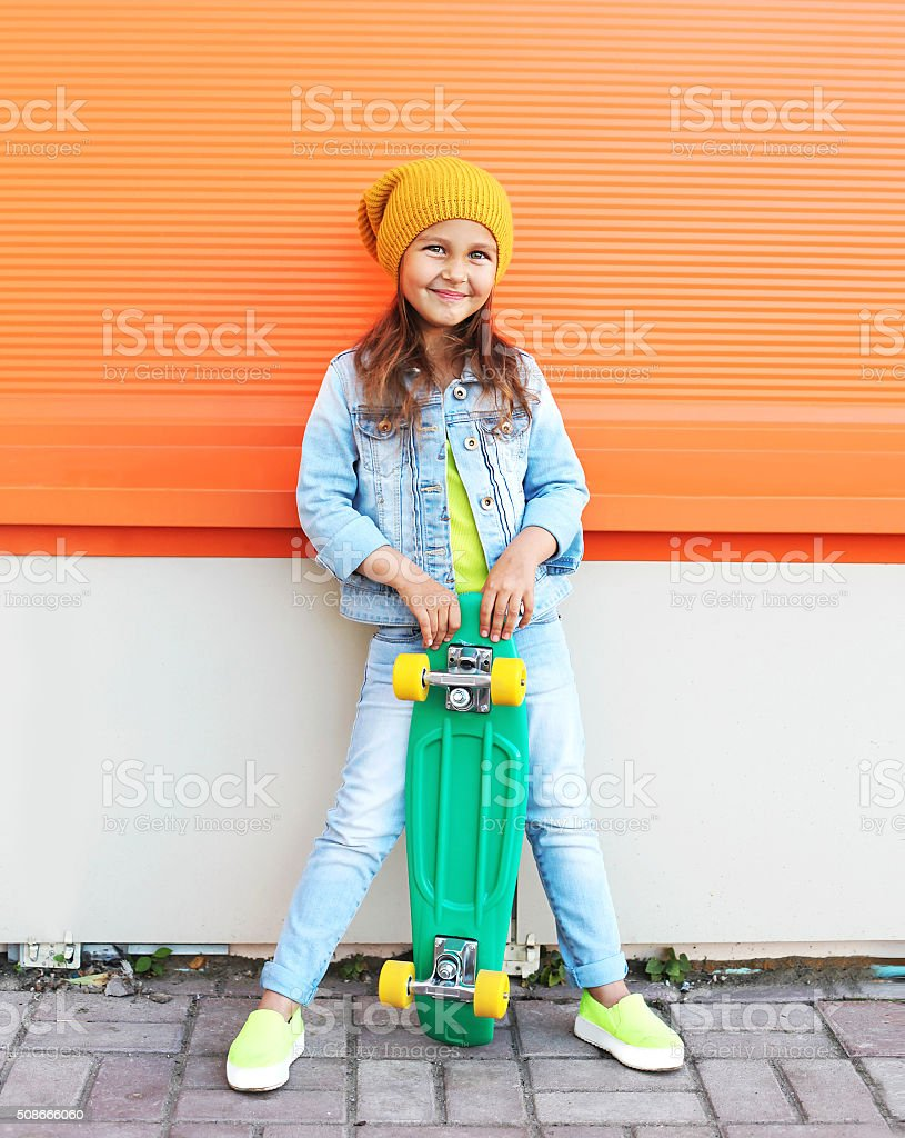 Stylish little girl child with skateboard having fun in city stock photo