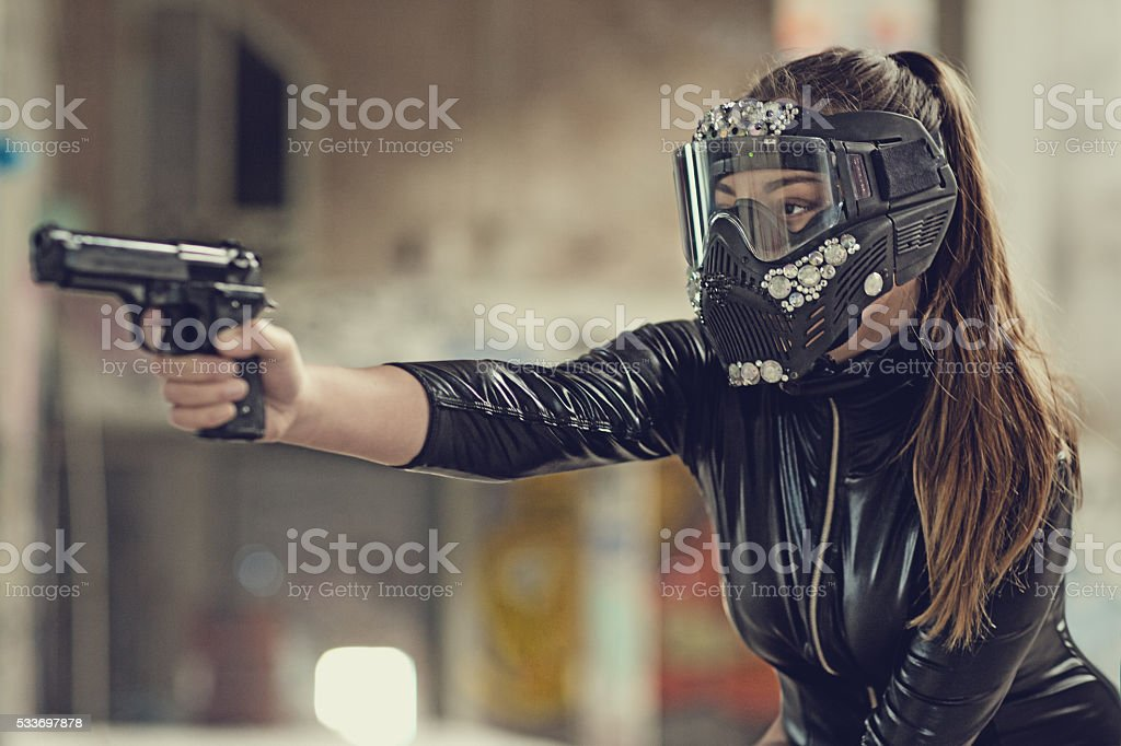 Stylish long haired armed brunette woman wearing a bejewelled mask stock photo