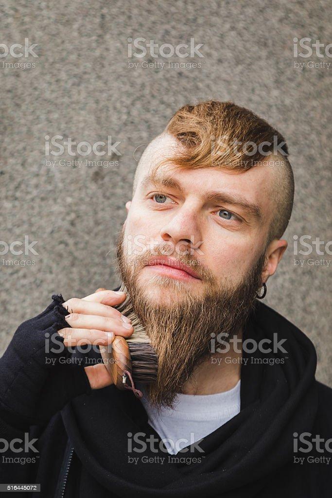 Stylish man brushing his beard stock photo