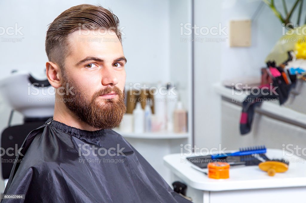 Stylish man in a barber shop looking at camera. stock photo